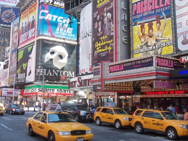 Broadway signs featuring a variety of shows and many yellow taxis on the street