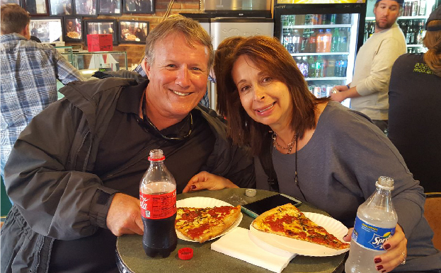 A man and woman enjoying pizza slices with soda