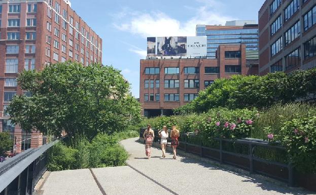Three people walkig through the High Line